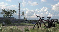 Bike stands in background of factory pipes and cranes, blue sky, 4K Stock Footage