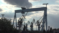 Shipbuilding cranes on a background of a stormy sky, stormy weather, 4K - stock footage