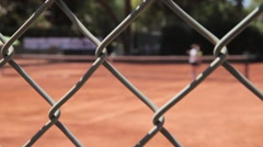 tennis court fence with people playing tennis behind - stock footage