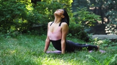 Beautiful young woman doing stretching yoga exercise on green grass at park - stock footage