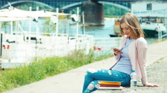 Young adult using mobile phone outdoors near river. Smiling at camera - stock footage