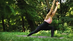 Beautiful young woman doing stretching yoga exercise on green grass at park Stock Footage