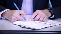Hands male businessman close-up, making notes in the phone book. - stock footage