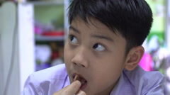 Little Asian child enjoys eating and watching television Stock Footage