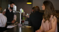 4K Woman waiting alone in bar for a friend or date who is late checks her phone Stock Footage