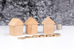 Three houses made of wooden blocks with coins: investing Stock Photos
