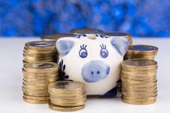 Piggy bank with stack of coins and blurry background Stock Photos