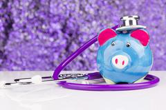 Piggy bank with a stethoscope: health insurance Stock Photos
