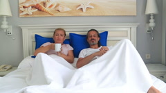 Couple lying on a bed watching tv together 2 Stock Footage