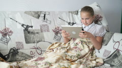 Teenager girl lying on a bed with a digital tablet Stock Footage