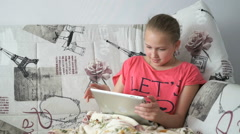Child lying on the bed with a digital tablet Stock Footage