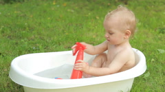 One year old kid having a bath outdoors Stock Footage