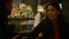 4K Female friends chatting & bartender serving drinks in trendy city bar Stock Footage