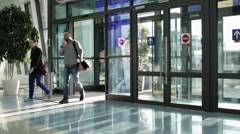 Man and woman come in the sliding door of the airport. Stock Footage