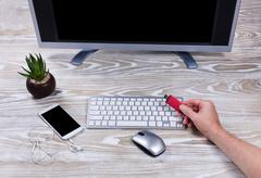 Hand holding data thumb drive with office desktop setup in background - stock photo