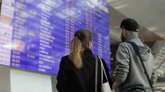 Guy and girlfriend stand near a large information screen in the airport. Stock Footage