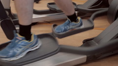 The member of the sports club train on the elliptical trainer in the gym Stock Footage
