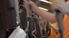 The members of the sports club train on the elliptical trainer in the gym Stock Footage