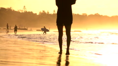 SLOW MOTION: Surfers on the beautiful beach at fantastic golden sunset in summer Stock Footage