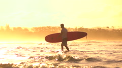 SLOW MOTION: Tall longboard surfer carrying board and walking in shallow water Stock Footage