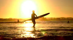 SLOW MOTION: Surfers spending summer vacation on surfing beach at golden sunset Stock Footage
