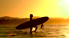 SLOW MOTION: Young unrecognizable female with longboard surf walking into ocean Stock Footage