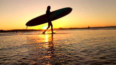 SLOW MOTION DOF: Unrecognizable female with longboard surf walking into ocean Stock Footage