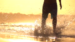 SLOW MOTION: Young sportsman jogging in shallow water on beautiful sunset beach Stock Footage