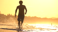 SLOW MOTION: Young sportsman running in shallow water on beautiful sunset beach - stock footage