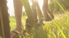 Slow motion man rides a bike through the tall grass, close-up Stock Footage