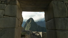 Huayna picchu framed by a stone doorway at machu picchu Stock Footage