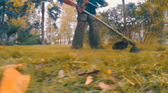 Employee with manual petrol lawnmower is mows the lawn Stock Footage