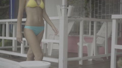 Pretty young woman wearing bikini petting cat on the terrace of pink house. Stock Footage