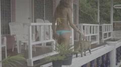 Pretty young woman wearing bikini walking with cat on the terrace in slow motion - stock footage