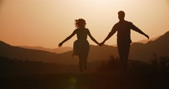 Couple silhouette running forward holding hands with the sunset Golden hour, the Stock Footage