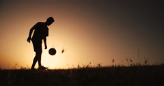 Football player silhouette , practicing with the ball,the sunset Golden hour Stock Footage