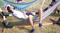 Young people guys sway relax in hammock during open air music festival Stock Footage