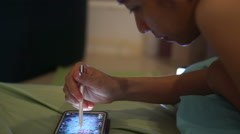 Woman laying on bed and playing games on smart phone at night - stock footage