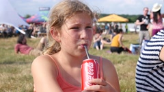 Cute little blonde girl drinking a bubbling drink from stick on festival picnic Stock Footage