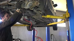 Portrait of mechanic with pneumatic wrench tool repairing car in his garage - stock footage