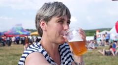 Adult woman drinking beer enjoying visiting open air festival Stock Footage