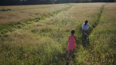 4K Camera moves to follow two children running through a meadow Stock Footage