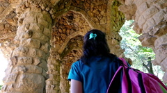 Woman admires arch of colonnaded path in Antoni Gaudi's Park Guell, Barcelona Arkistovideo