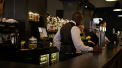 4K Portrait of smiling barman standing behind counter in fashionable city bar Stock Footage