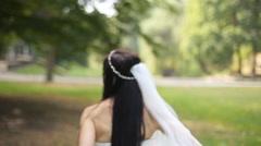 Bride in wedding dress walking on grass on a breezy day - stock footage