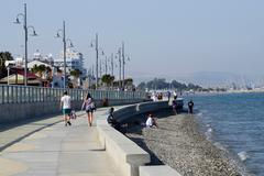 View of Larnaca seafront with palm trees , pedestrians and beach,Cyprus Stock Photos