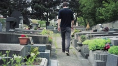Man Walks By Tombs In The Cemetery - stock footage
