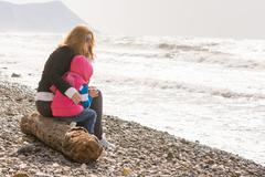 My mother and five year old daughter sitting on the beach, my mother hugged h - stock photo