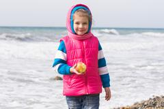 Portrait of a five year old girl with an apple on the beach - stock photo