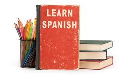 Learn spanish language. school supplies on white Stock Photos